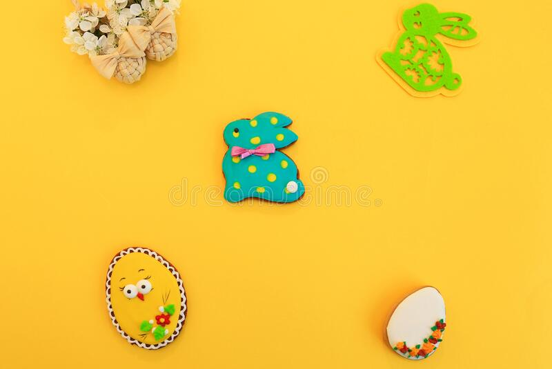Handmade multi-colored gingerbread cookies in the form of a bunny and Easter eggs, straw shoes and flowers on a yellow background. Gingerbread Easter Bunny royalty free stock images