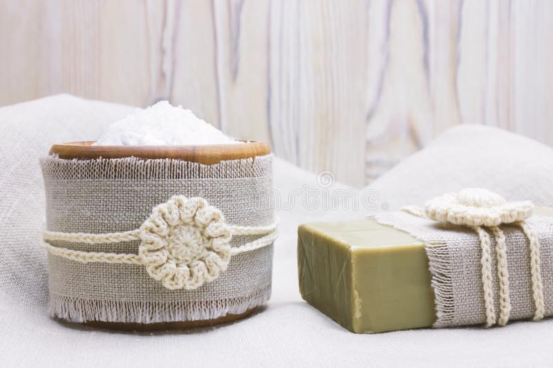 Handmade, natural organic olive oil soap and cosmetic salt on linen and wooden background. Spa bath accessories, feminine care pro. Handmade, natural organic stock photos