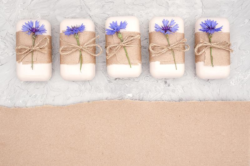 Handmade natural soap set decorated with craft paper, scourge and blue flowers. Organic cosmetics concept. Top view Flat lay Copy royalty free stock photos