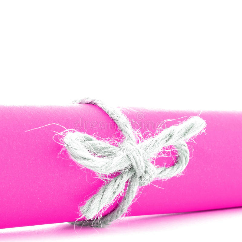 Handmade natural string knot tied on pink paper roll isolated royalty free stock image