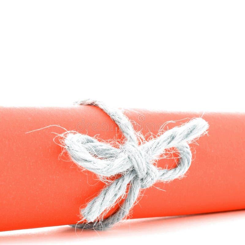 Handmade naturalny linowy guzek wiążący na pomarańcze papieru tubce odizolowywającej fotografia royalty free