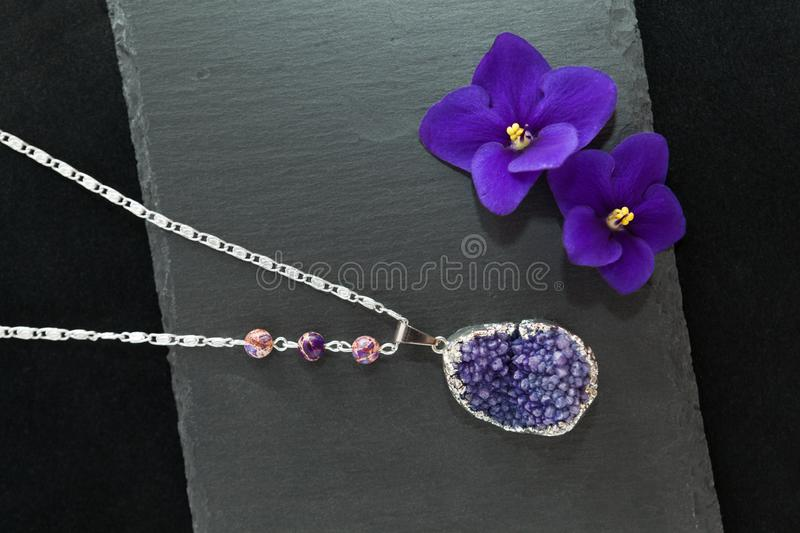 Handmade necklace with druzy violet agate. Beautiful handmade silver necklace with crystal druse violet gemstone agate and purple beads of jasper, lying flat on royalty free stock image