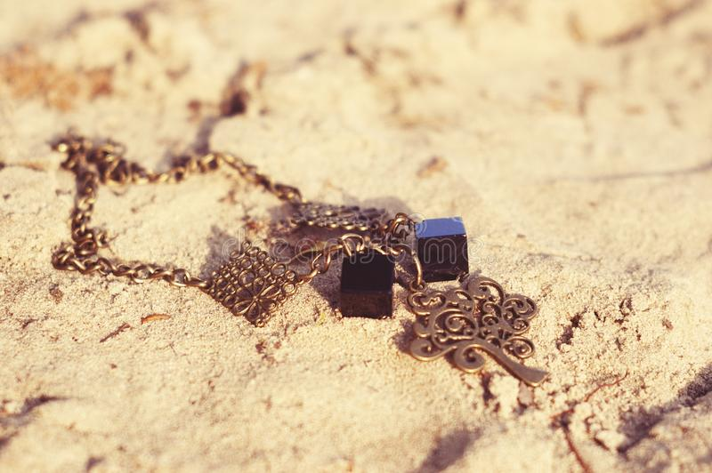 Handmade. Necklace on the sand on unny day royalty free stock images