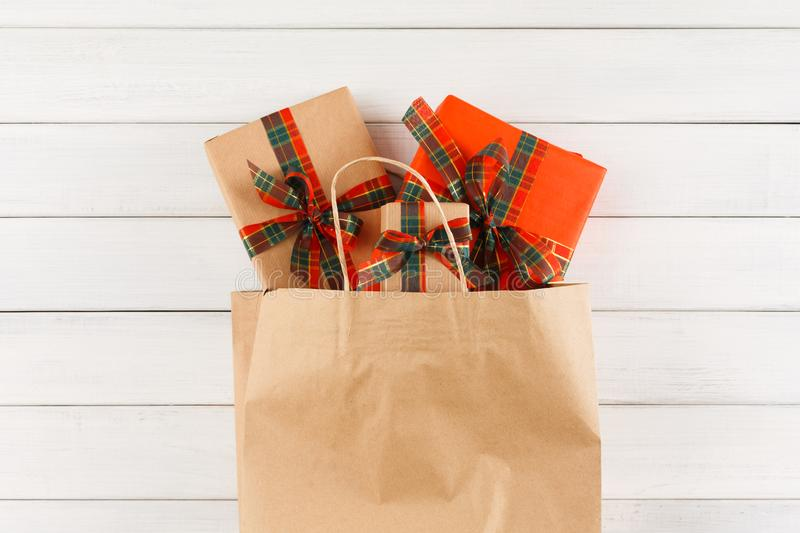 Creative christmas gifts in paper bag on white wood table background stock photography