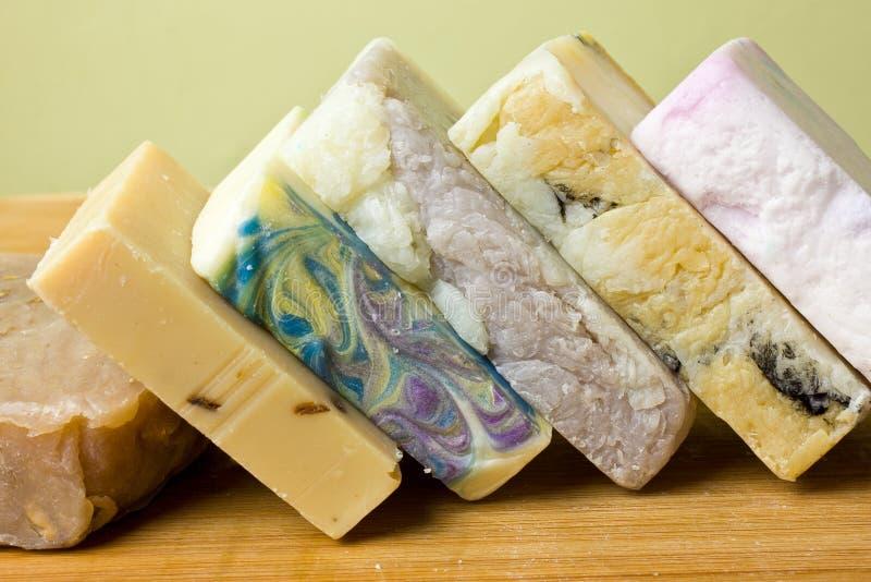 Colorful Handmade Oatmeal Soap Bars. Homemade oatmeal, honey, & shea butter soap bars on a wooden counter royalty free stock photo