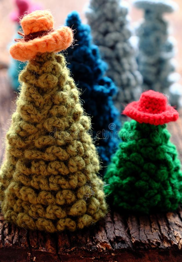 Handmade ornament for wintertime, crochet Christmas tree wear colorful hat on dark background royalty free stock photo
