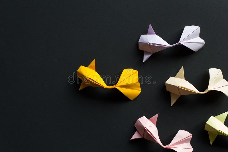 Handmade paper craft origami gold koi carp fishes on black background.Top view, pattern royalty free stock images