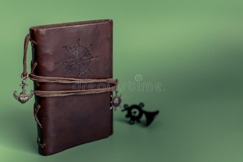 Handmade paper diary Notepad in brown leather case on green Christmas background royalty free stock photos
