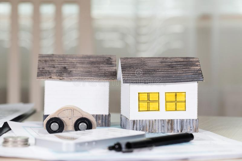 Handmade paper houses on the table. Papers,pen,calculator,coins. In the background. Closeup stock image