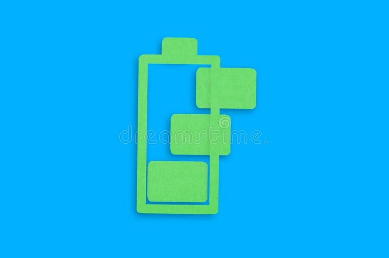Handmade paper icon of charging battery with green cells in center of blue table. Top view stock illustration