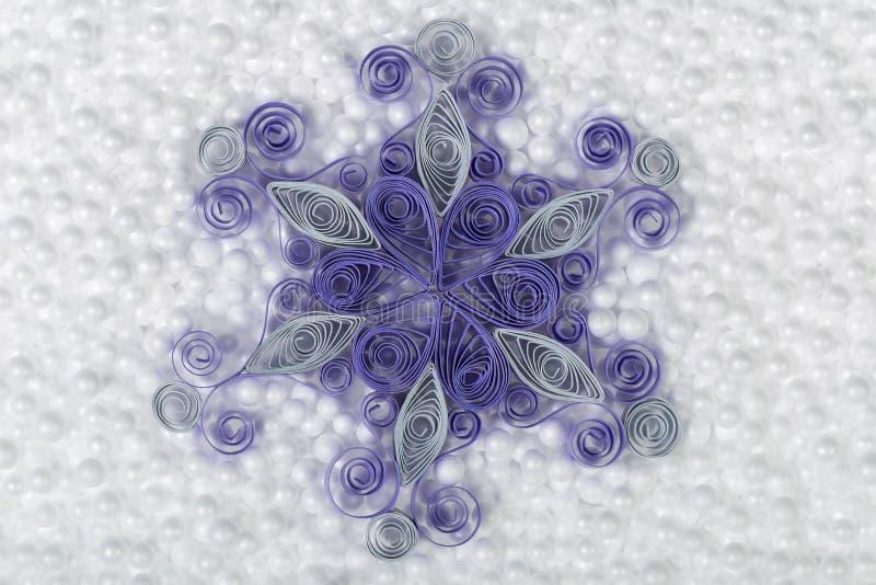 Handmade paper snowflake on white styrofoam background. royalty free stock photography