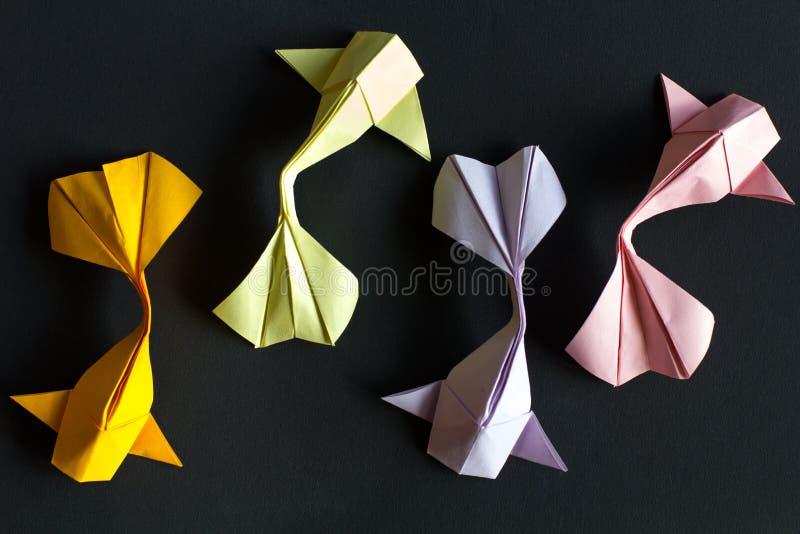 Handmade papierowego rzemiosła origami złocisty koja i menchia, zieleń, fiołkowy karp łowimy na czarnym tle Widok z góry, wzór zdjęcia royalty free