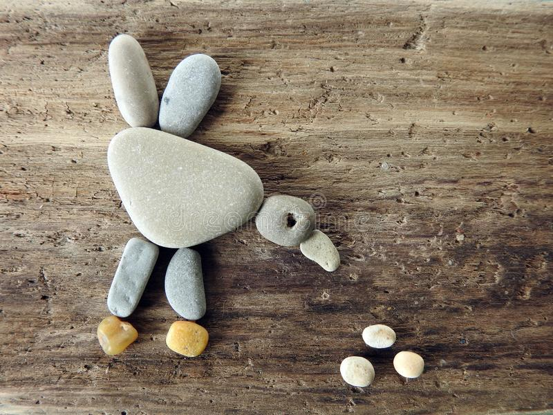Handmade picture - bird  on wooden surface, Lithuania. Handmade picture - bird - using sea stones and sea wood stock photo