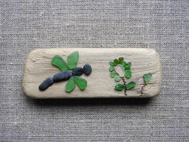Handmade picture- dragonfly and flower , using sea glass and wood, Lithuania stock image