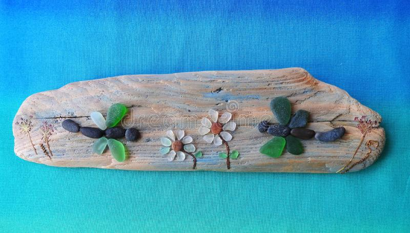 Handmade picture - Dragonfly and flowers on wooden surface, Lithuania stock image