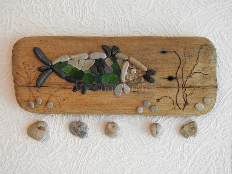 Handmade picture- fish , using sea stones, sea glass and wood, Lithuania royalty free stock images