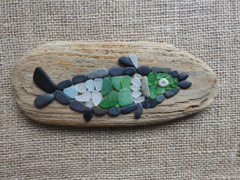 Handmade picture- fish , using sea stone, glass and wood, Lithuania royalty free stock photo