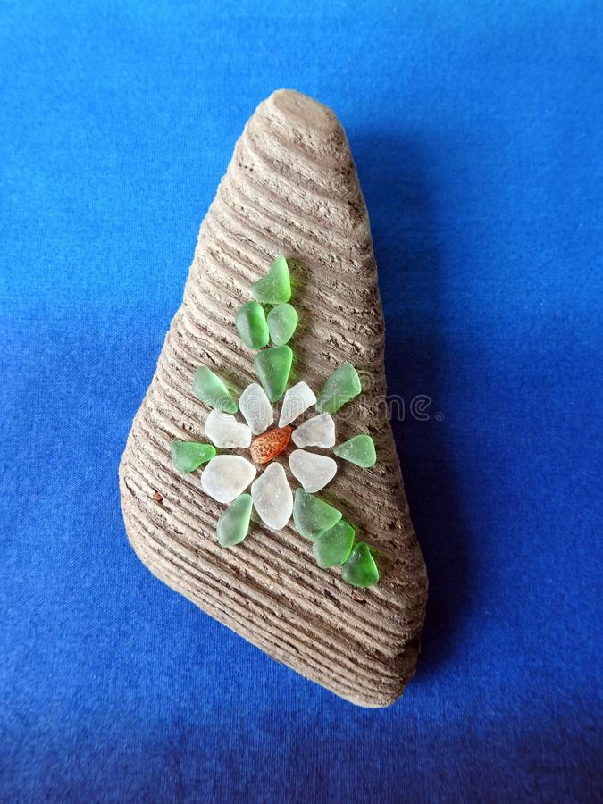 Handmade picture- flower , using sea glass and wood, Lithuania. Handmade picture - flower using sea wood, sea amber and sea glass royalty free stock photo