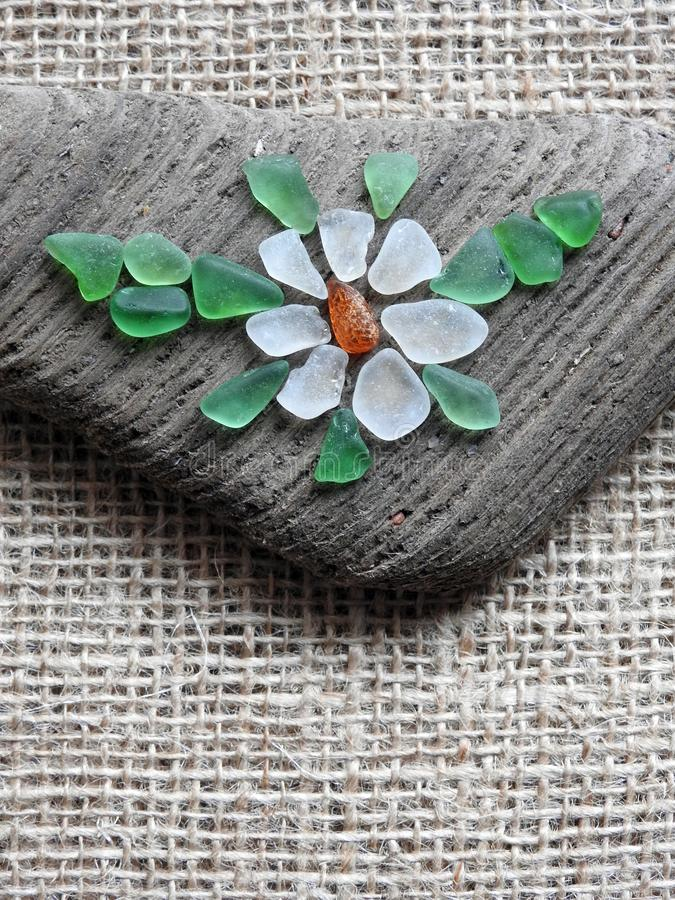 Handmade picture- flower , using sea glass and wood, Lithuania. Handmade picture - flower using sea wood, sea amber and sea glass on linen background stock photos
