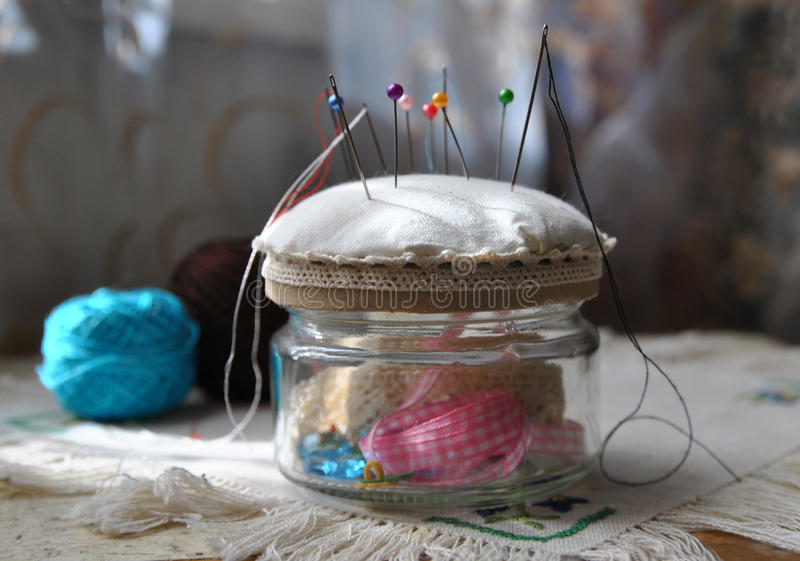 Handmade pincushion. From an unnecessary glass jar, soft focus in background stock photos