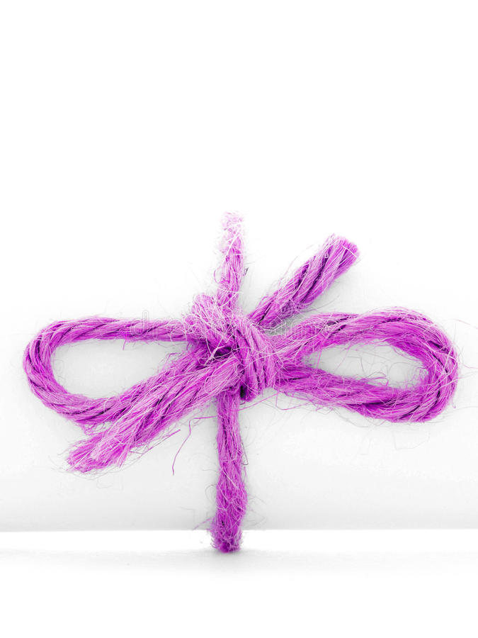 Handmade pink string bow tied on white letter tube isolated royalty free stock images