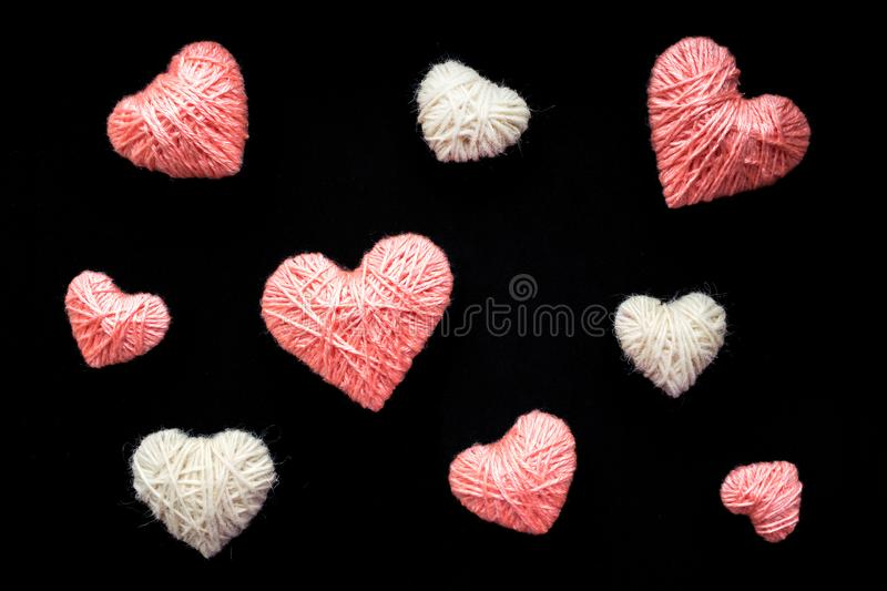 Handmade pink and white wool yarn heart isolated on black. Many. Pink and white hearts of knitting threads background. Symbol of love. Hobby, love and romance royalty free stock photos