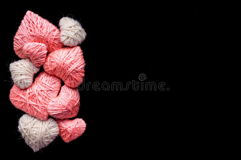 Handmade pink and white wool yarn heart isolated on black. Many. Pink and white hearts of knitting threads background with copyspace. Symbol of love. Hobby royalty free stock images