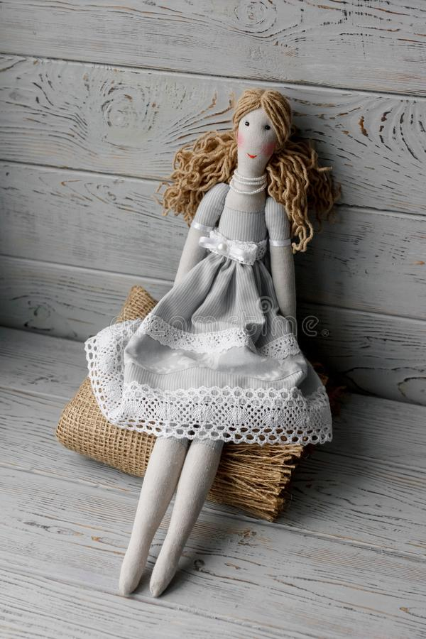 Handmade real life doll on a tablecloth with roses stock photo