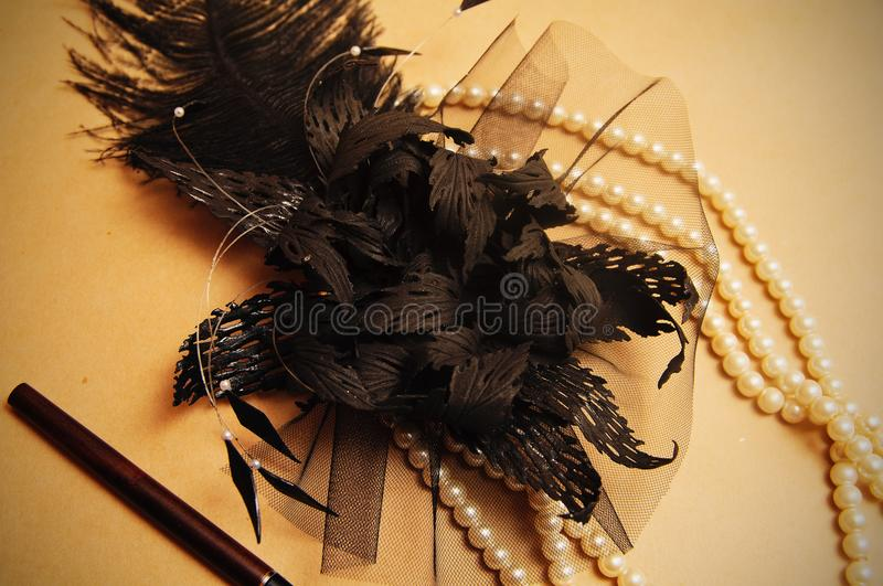 Handmade retro hair ornament. From feathers necklace and a tube for cigarettes royalty free stock image