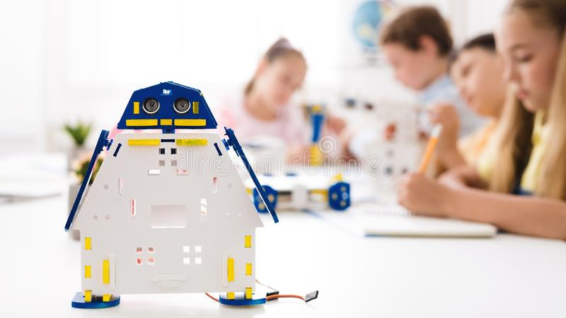 Handmade robot at desk with schoolchildren at background royalty free stock photos