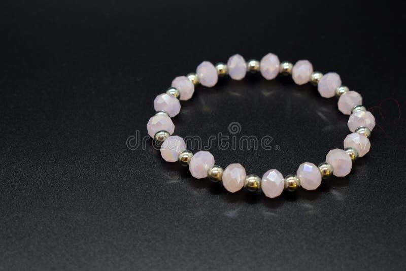 Handmade rose quartz bracelet with silver beads on a dark background royalty free stock image