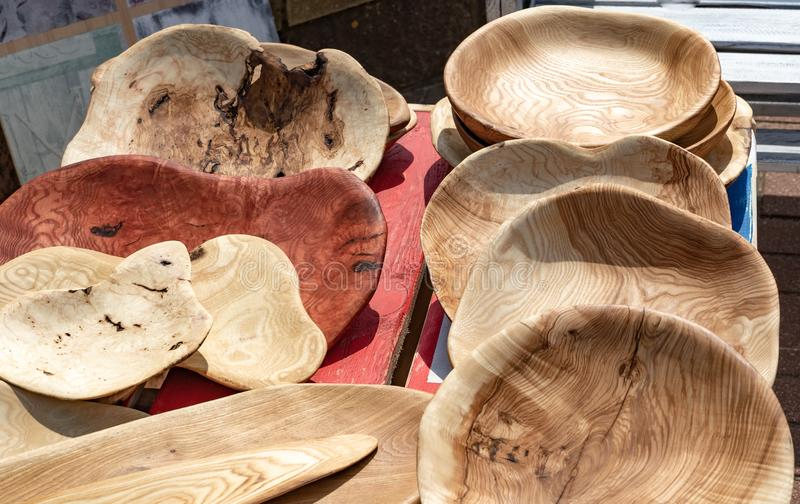 Handmade rustic wooden plates on the street market. Wooden goods are exhibited for sale stock photos
