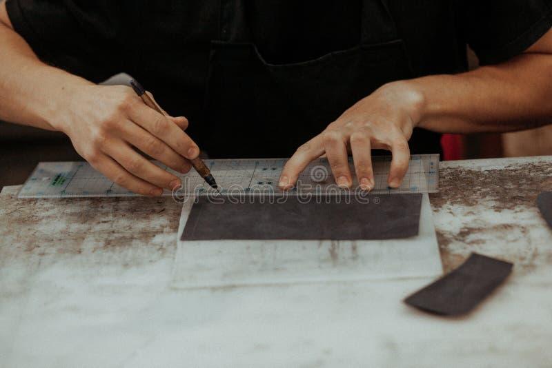 Handmade rzemienny rzemieślnik robi rzemiosło portflowi na jego pracującym miejscu z narzędziami używać kawałek naturalna skóra,  obraz stock