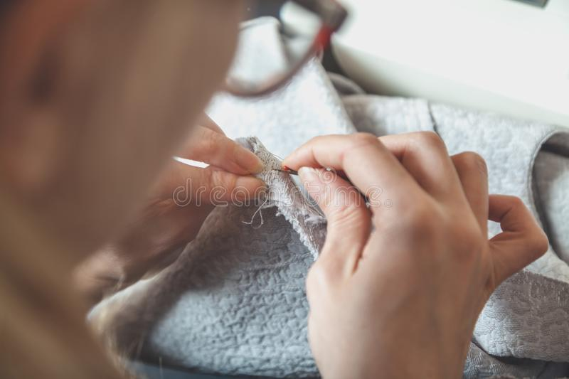 Handmade. seamstress makes seam with needle and thread. We sew with our hands. A woman stitches a piece of soft cloth with a needle and thread stock photography