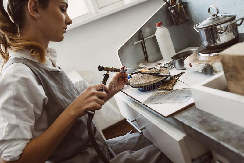 Handmade. Side view of young female jeweler soldering a silver earring with flame from welding torch stock images