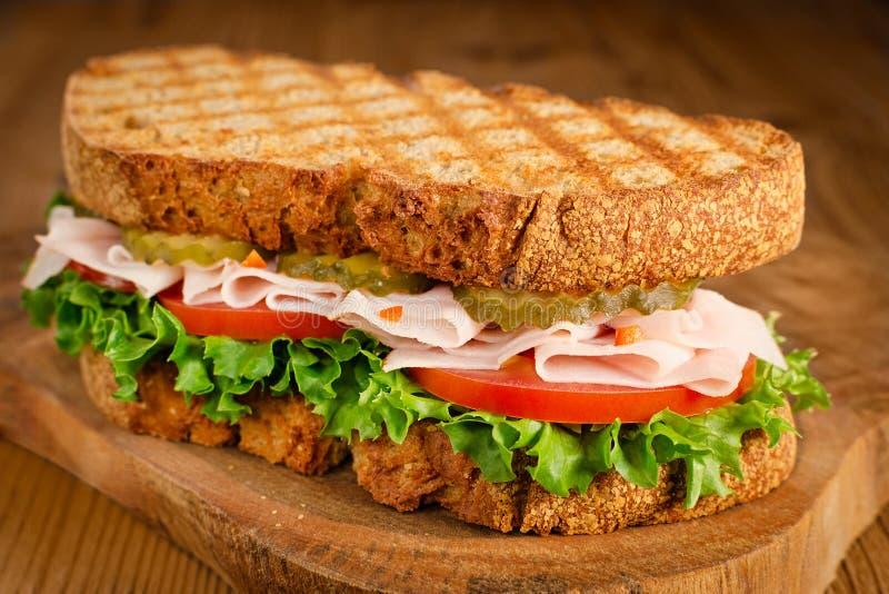 Handmade smakowita indycza kanapka z pomidorem, sałatką i ogórkiem, na drewnianym tle obraz royalty free