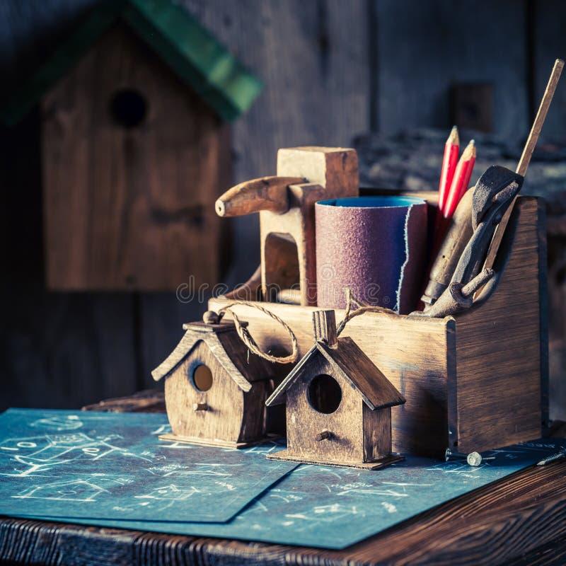 Handmade small bird house and blue construction plan. Closeup of handmade small bird house and blue construction plan royalty free stock images