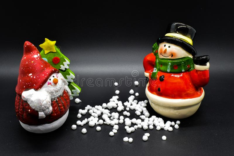 Handmade snowmen figurines isolated on black background. Christmas decoration. stock photo