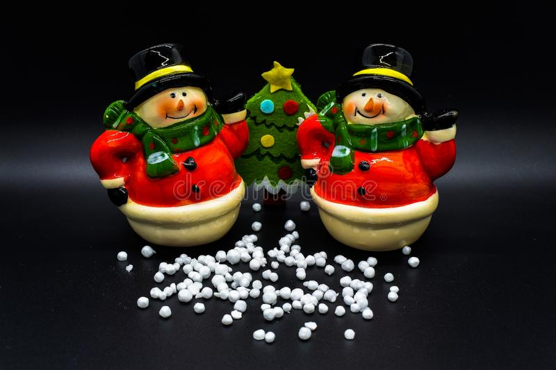 Handmade snowmen figurines isolated on black background. Christmas decoration. stock photography