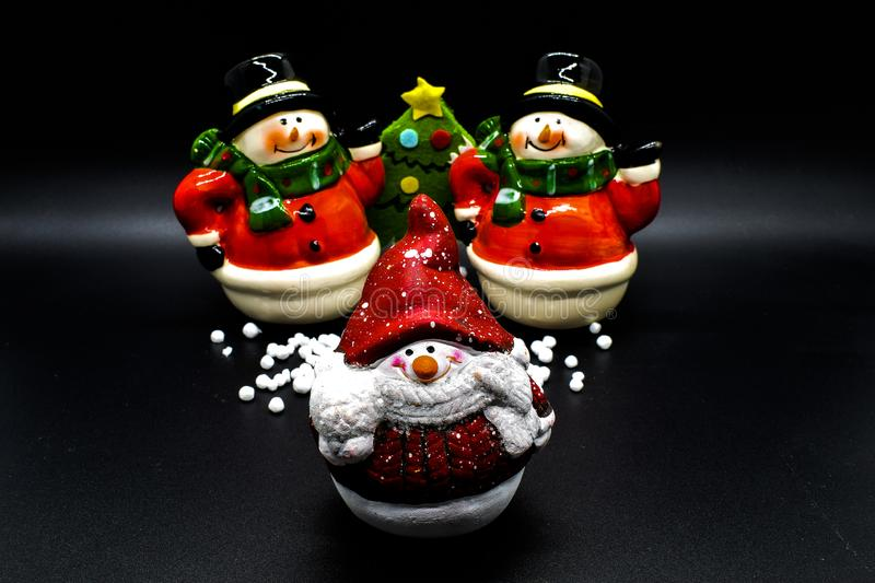 Handmade snowmen figurines isolated on black background. Christmas decoration. stock photos