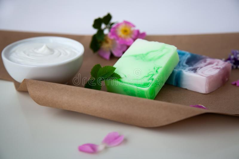 Handmade soap on the craft paper. With flowers and cream royalty free stock images