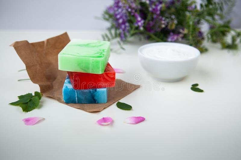 Handmade soap on the craft paper. With flowers and cream stock photography