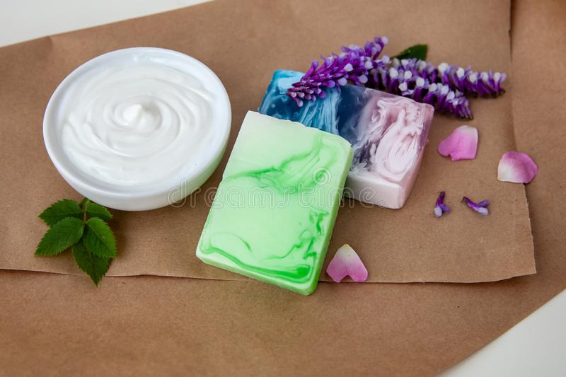 Handmade soap on the craft paper. With flowers and cream royalty free stock image