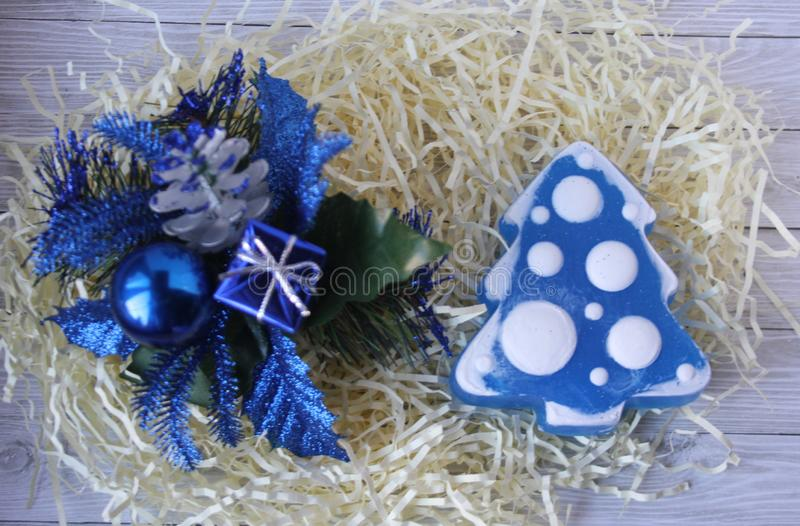 Handmade soap in the shape of a Christmas tree and blue Christmas decorations on a light background. royalty free stock photo