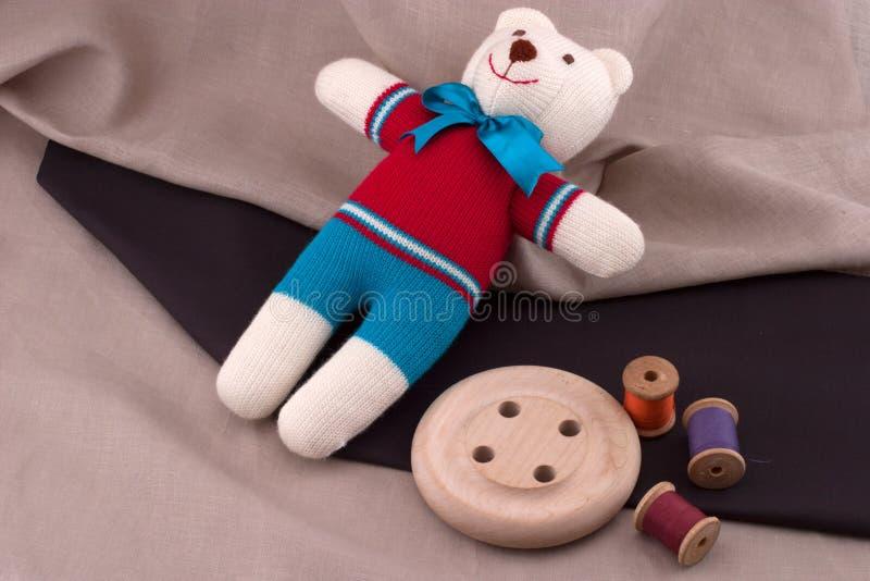 Handmade teddy bear and a thread stock photography