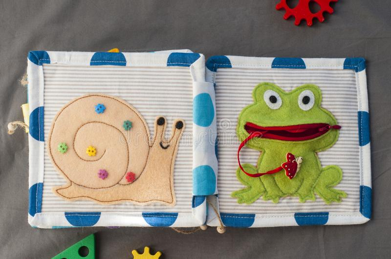 Handmade textile book for baby on gray background. Pages with funny felt snail and frog. Woolly toys teaching to use zipper. royalty free stock photo