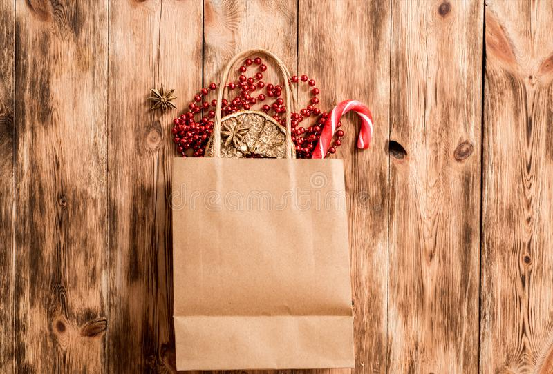 Handmade tinkered advent calendar with paper bags and stickers. Golden metal beads, orange, and golden branch of spruce. On a wooden background. copy space royalty free stock image