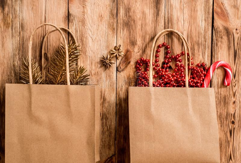 Handmade tinkered advent calendar with paper bags and stickers. Golden metal beads, orange, and golden branch of spruce. On a wooden background. copy space stock photos