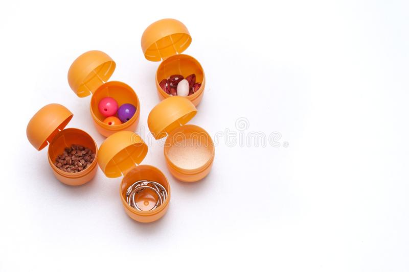 Handmade toy for hearing development. Containers with buckwheat, beans, beads, semolina on white background. Handmade toy for hearing development. Plastic stock photos