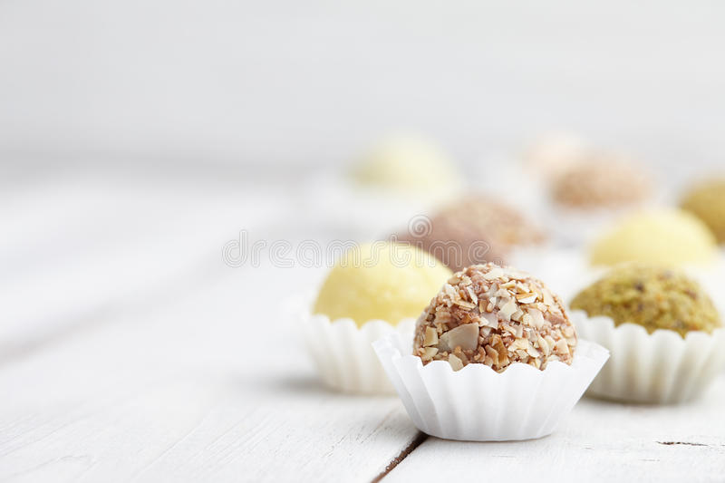 Handmade truffle chocolates. Chocolate truffle candies with nuts on white wooden background royalty free stock images